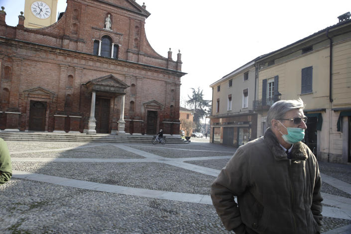 A man wearing a mask stands in front of the San Biagio church in Codogno, near Lodi, Northern Italy, Saturday, Feb. 22, 2020. A dozen towns in northern Italy are on effective lockdown after the new virus linked to China claimed a first fatality in Italy and sickened an increasing number of people. The secondary contagions have prompted local authorities in towns of Lombardy and Veneto to order schools, businesses, and restaurants closed, and to cancel sporting events and Masses. (AP Photo/Luca Bruno)