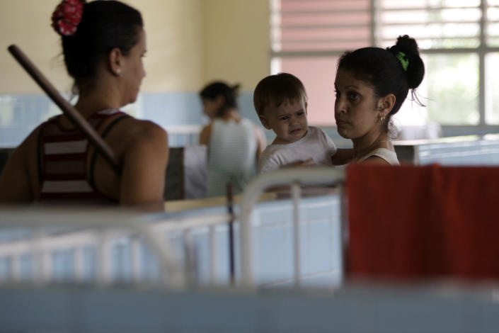 In this March 31, 2012 photo, people stand in the government-run Jose Luis Miranda Children's Hospital in Santa Clara, Cuba. Cuba's system of free medical care, long considered a birthright by its citizens and trumpeted as one of the communist government's great successes, is not immune to cutbacks under Raul Castro's drive for efficiency. The health sector has already endured millions of dollars in budget cuts and tens of thousands of layoffs, and Castro is looking for more ways to save. (AP Photo/Franklin Reyes)