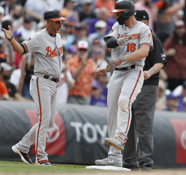 Baltimore Orioles third base coach Jose David Flores, left, celebrates with Trey Mancini (16) after Mancini's triple to drive in two runs off Colorado Rockies relief pitcher Bryan Shaw in the eighth inning of a baseball game Sunday, May 26, 2019, in Denver. (AP Photo/David Zalubowski)