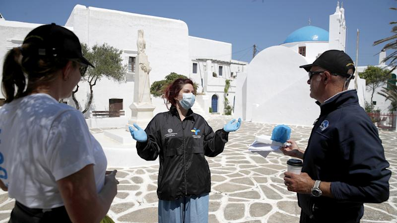 A Public Health Organisation doctor speaks with volunteers after residents were tested for coronavirus.