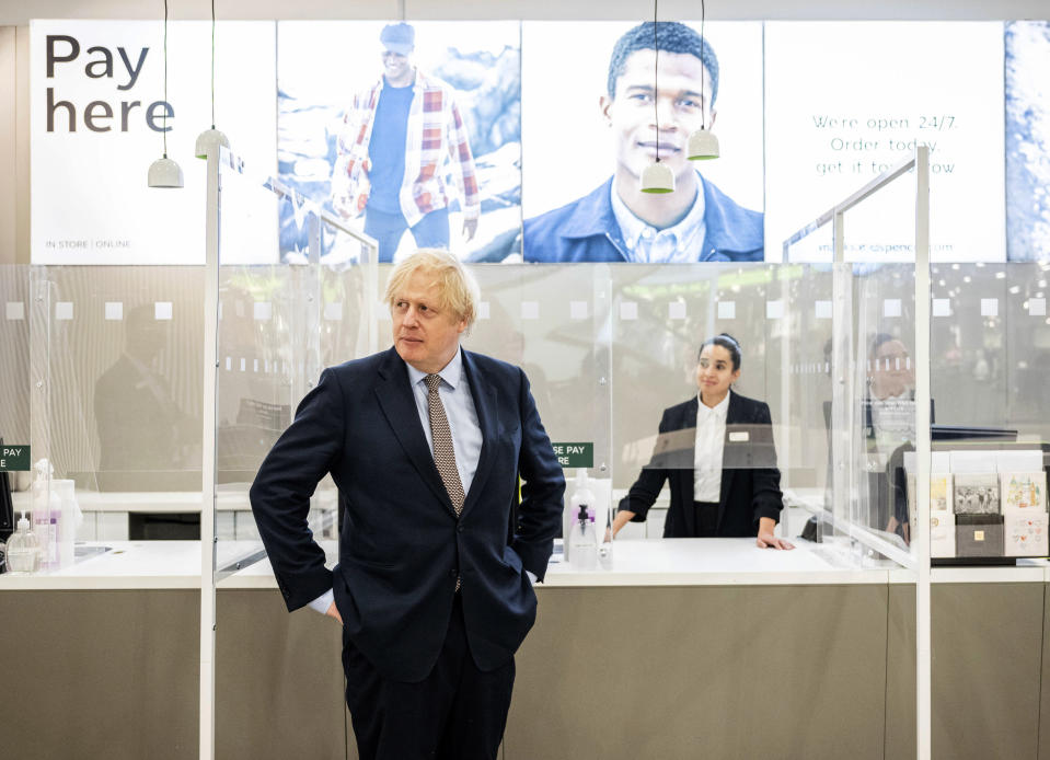 Britain's Prime Minister Boris Johnson visits a shop in Westfield Stratford shopping centre in east London, Sunday June 14, 2020, to see the preparations the stores are making to be COVID-19 secure, ahead of non-essential retail being able to reopen from Monday morning. (John Nguyen/Pool via AP)