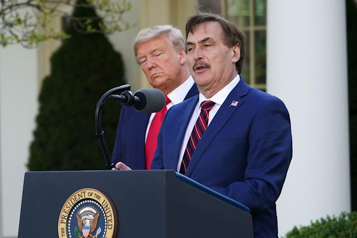 President Trump listens as Mike Lindell, CEO of MyPillow Inc., speaks during the daily coronavirus briefing at the White House on March 30. (Mandel Ngan/AFP via Getty Images)