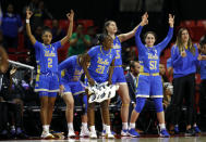 UCLA forward Michaela Onyenwere (21) celebrates with teammates after Japreece Dean scored a 3-pointer during the second half of a second-round game against Maryland in the NCAA women's college basketball tournament Monday, March 25, 2019, in College Park, Md. UCLA won 85-80. (AP Photo/Patrick Semansky)
