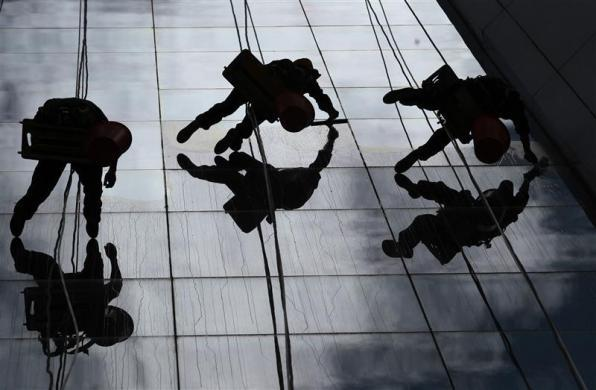 Workers clean the windows of a building in Quito September 7, 2011.