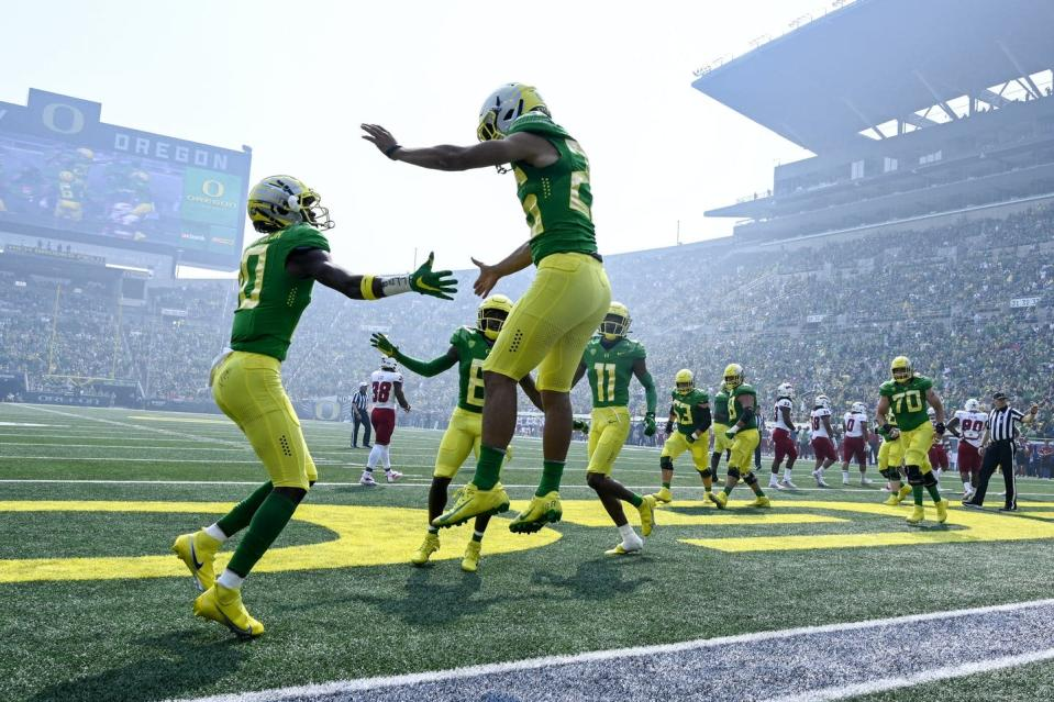 """<span class=""""caption"""">University of Oregon running back Travis Dye celebrates his touchdown against Fresno State in a stadium smokey from nearby wildfires.</span> <span class=""""attribution""""><span class=""""source"""">(AP Photo/Andy Nelson)</span></span>"""