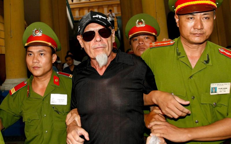 Fallen British glam rock star Gary Glitter (C) is escorted by police out of a courtroom after losing his appeal hearing in a child molestation case in Ho Chi Minh City, Vietnam - Credit: EPA