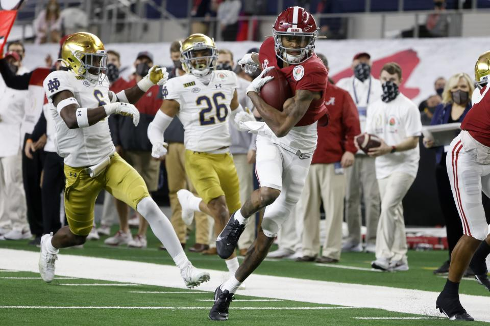 FILE - Alabama wide receiver DeVonta Smith (6) gets past Notre Dame linebacker Jeremiah Owusu-Koramoah (6) and cornerback Clarence Lewis (26) on his way to the end zone for a touchdown in the first half of the Rose Bowl NCAA college football game in Arlington, Texas, in this Friday, Jan. 1, 2021, file photo. The Heisman Trophy winner caught seven passes for 130 yards and three touchdowns as No. 1 Alabama beat No. 4 Notre Dame in a College Football Playoff semifinal.(AP Photo/Michael Ainsworth, File)