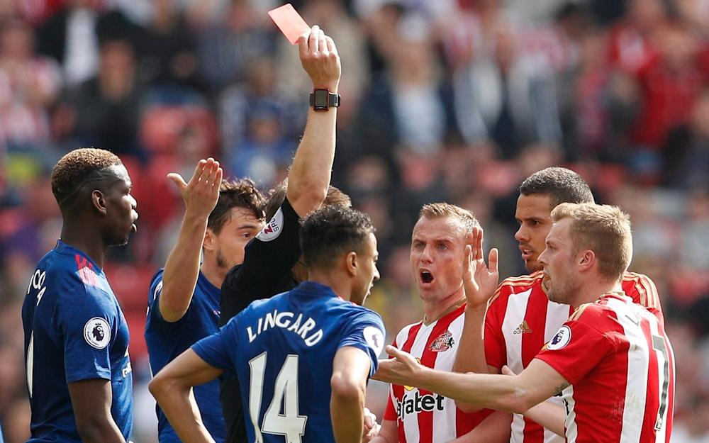 Referee Craig Pawson shows Sunderland's Larsson the red cars - Credit: Reuters