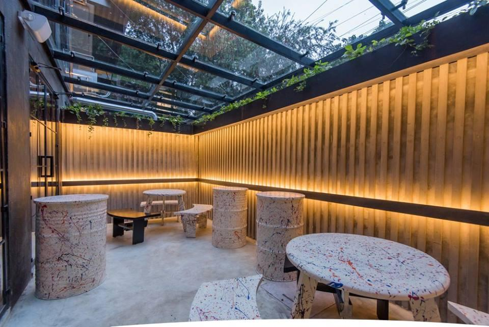 Ground floor outdoor seating/smoking zone with glazed pergola roof and cove lights highlighting the compound wall profile.