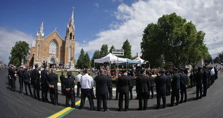 Emergency responders form an honor guard prior to a memorial mass at the Sainte-Agnes church in Lac-Megantic