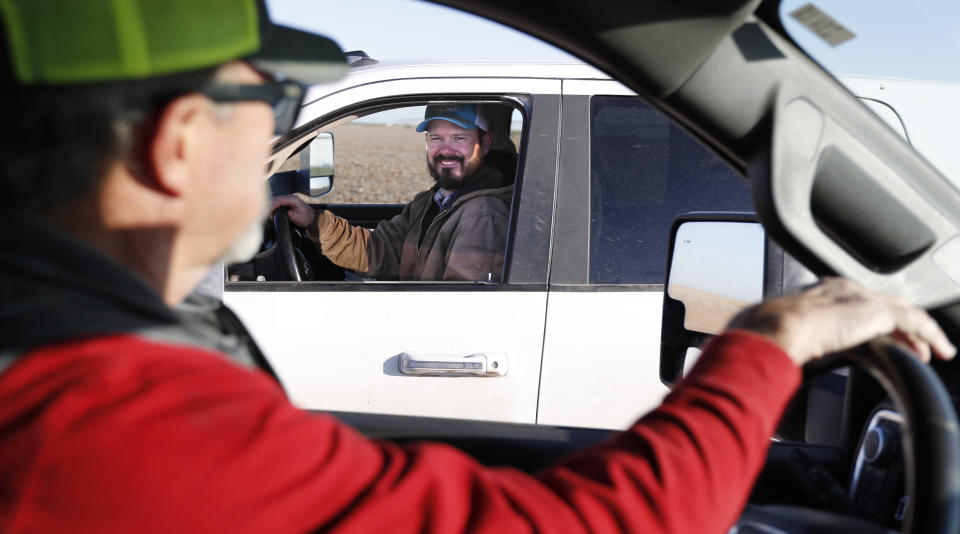 Tim Black, left, stops to talk to his son, Tyler, on their farm in Muleshoe, Texas, on Monday, April 19, 2021. The longtime corn farmers now raise cattle and have planted some land in wheat and native grasses because the Ogallala Aquifer, used to irrigate crops, is drying up. (AP Photo/Mark Rogers)