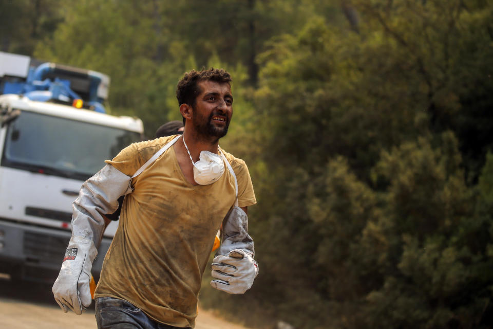 A Turkish volunteer runs as he heads to fight wildfires in Turgut village, near the tourist resort of Marmaris, Mugla, Turkey, Wednesday, Aug. 4, 2021. As Turkish fire crews pressed ahead Tuesday with their weeklong battle against blazes tearing through forests and villages on the country's southern coast, President Recep Tayyip Erdogan's government faced increased criticism over its apparent poor response and inadequate preparedness for large-scale wildfires.(AP Photo/Emre Tazegul)
