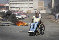 A protester in a wheelchair passes a burning tyre in Johannesburg, Sunday, July 11, 2021. Protests have spread from the KwaZulu Natal province to Johannesburg against the imprisonment of former South African President Jacob Zuma who was imprisoned last week for contempt of court. (AP Photo/Yeshiel Panchia)