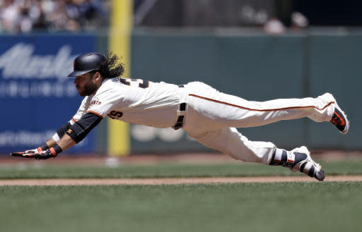 San Francisco Giants' Brandon Crawford slides safety into third base with an RBI-triple during the fourth inning of a baseball game against the San Diego Padres, Saturday, June 23, 2018, in San Francisco. (AP Photo/Marcio Jose Sanchez)