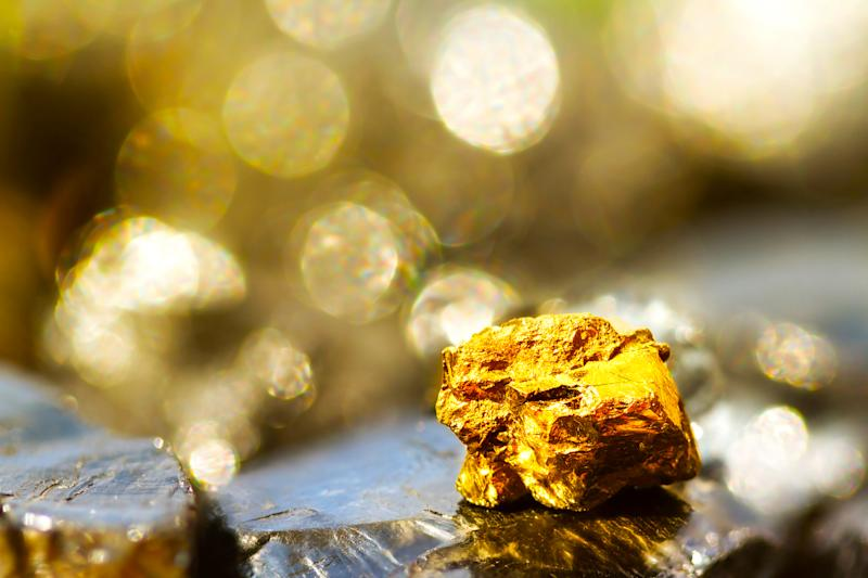 Golden bar on raw coal nuggets with soft focus and shiny background