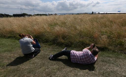 Spectators take photographs of the course during a practice day ahead of the British Open Golf championship at the Royal Liverpool golf club, Hoylake, England, Tuesday July 15, 2014. The British Open Golf championship starts Thursday July 17. (AP Photo/Jon Super)