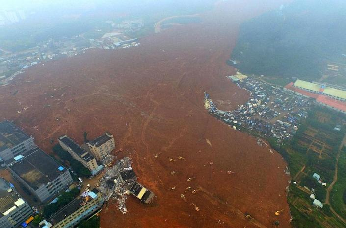 Rescuers searching a Chinese industrial park swamped by a weekend landslide have recovered the first body, as hopes fade for dozens of people still missing in the mud (AFP Photo/)