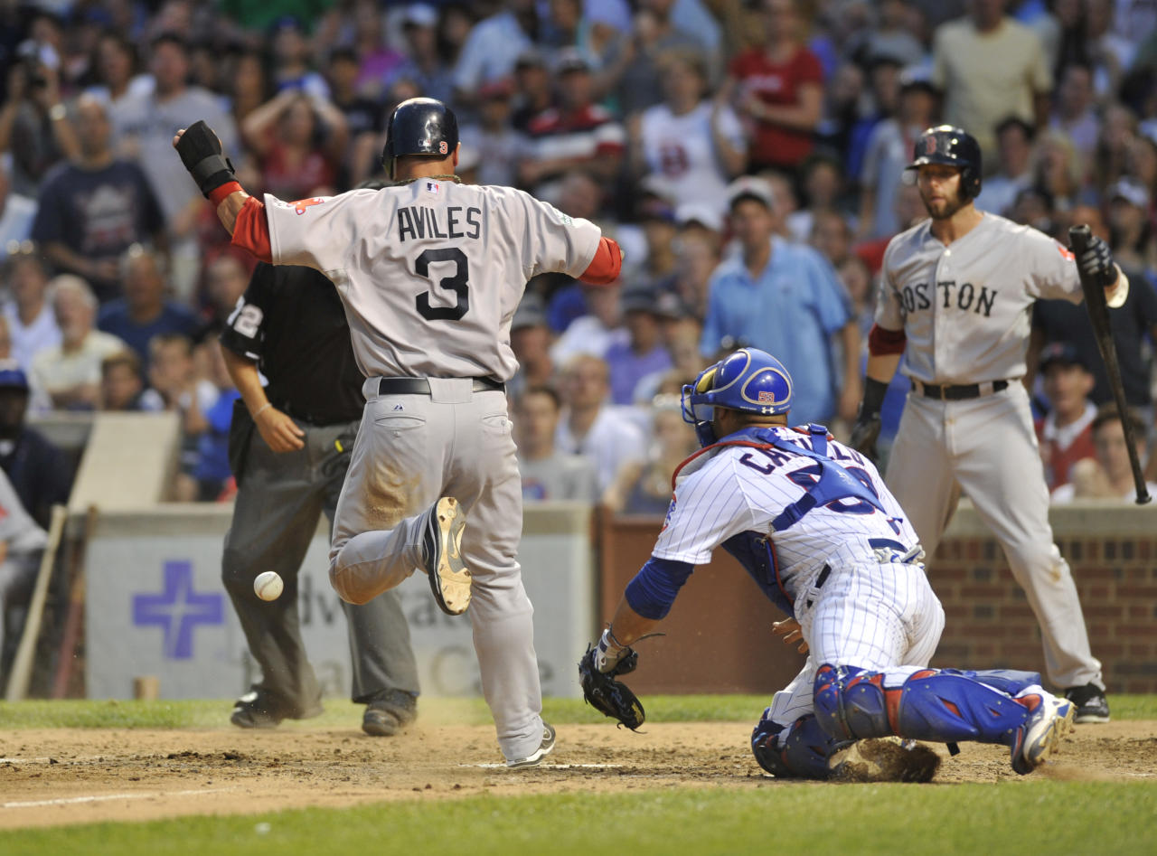 CHICAGO, IL - JUNE 16: Mike Aviles #3 of the Boston Red Sox scores as Welington Castillo #53 of the Chicago Cubs takes the throw in the seventh inning on June 16, 2012 at Wrigley Field in Chicago, Illinois.  (Photo by David Banks/Getty Images)