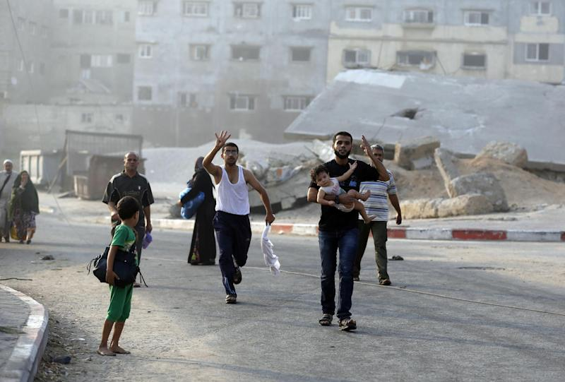 Palestinians flee their homes in Gaza's eastern Shejaiya district on July 20, 2014 following heavy Israeli shelling