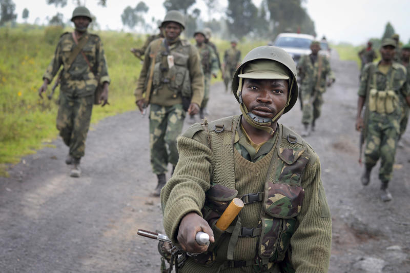 """FILE - In this Monday, Oct. 28, 2013 file photo, Congolese army soldiers march into Kibumba town after recapturing it from M23 rebels over the weekend, around 25km from the provincial capital Goma, in eastern Congo. A Congolese rebel group whose fighters retreated into Uganda after being hammered by U.N.-backed Congolese government forces """"can still regroup,"""" a Ugandan government spokesman said Tuesday, Nov. 12, 2013. The warning came after Congolese government officials delayed signing a peace accord with the insurgents. (AP Photo/Joseph Kay, File)"""