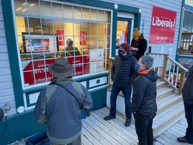 Liberal Leader Sandy Silver (centre) watches results pour in from outside the Liberal Party HQ in Dawson City, Yukon, Monday night.