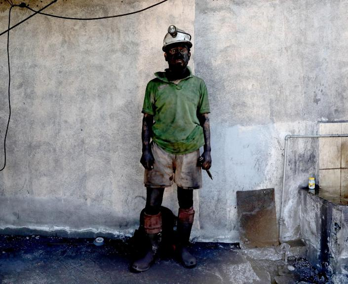 A coal miner with face, arms and legs covered in soot