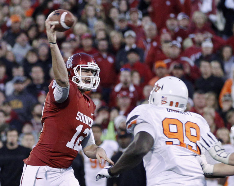 Oklahoma quarterback Landry Jones (12) passes for a 2-point conversion under pressure from Oklahoma State defensive tackle Calvin Barnett (99) in the fourth quarter of an NCAA college football game in Norman, Okla., Saturday, Nov. 24, 2012. Oklahoma won in overtime, 51-48. (AP Photo/Sue Ogrocki)