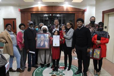 Reco pictured with family and friends, as well as a framed photo of his late mother Deborah Watson, after his proclamation recognition.