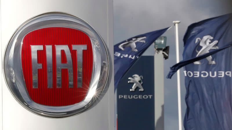 FILE PHOTO: The logos of car manufacturers Fiat and Peugeot are seen in front of dealerships of the companies in Saint-Nazaire