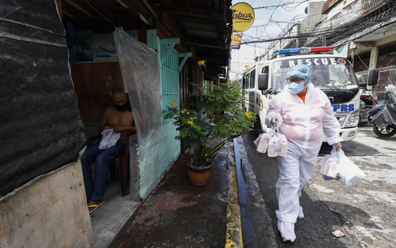 A city worker wearing a protective suit (R) goes around to handout free medicine and vitamins at a village under quarantine protocols in Caloocan City, Metro Manila, Philippines - ROLEX DELA PENA/EPA-EFE/Shutterstock