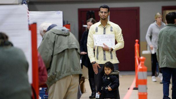 PHOTO: Luis Sanchez waits for a booth to open up as he votes with his daughter Sophia 2, at the Saco Community Center, Nov. 6, 2018, in Saco, Maine. (Portland Press Herald via Getty )