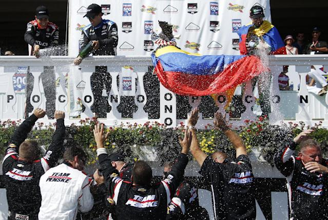 From top left to right, Helio Castroneves, of Brazil; Juan Pablo Montoya, of Colombia; and Carlos Munoz, also of Colombia, celebrate in Victory Lane with Montoya's crew after the Pocono IndyCar 500 auto race on Sunday, July 6, 2014, in Long Pond, Pa. Montoya won the race, Castroneves finished second and Munoz finished third. (AP Photo/Matt Slocum)