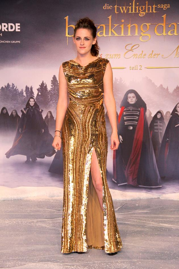 Kristen Stewart looked amazing in this gold dress with a thigh-high split at the Berlin photocall for Twilight: Breaking Dawn Part 2. Copyright [WENN]
