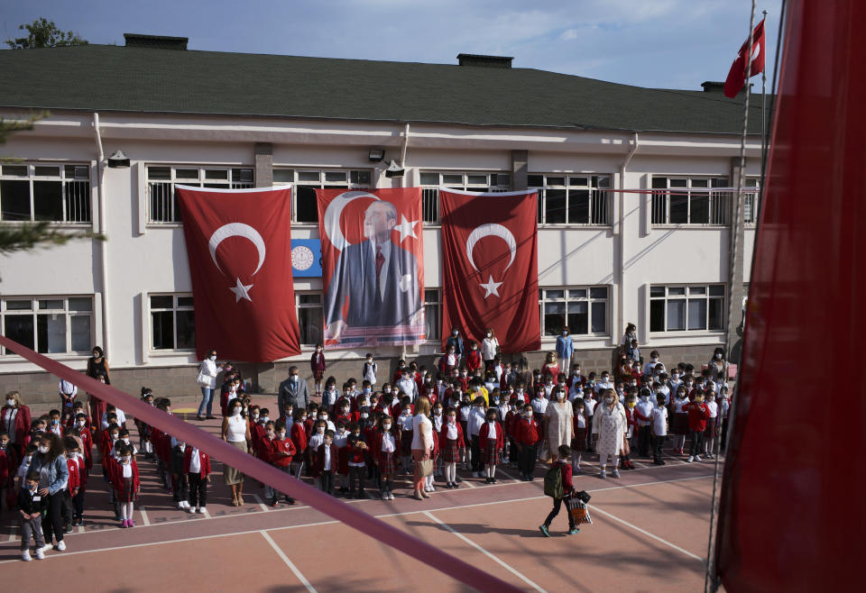 Pupils and teachers stand to sing the Turkish national anthem before the first classes as they arrive back at Cankaya Primary School in Turkish capital Ankara as schools reopen after 18 months' closure due to COVID-19, Monday, Sept. 6, 2021. The Turkish government has decided to reopen schools and colleges in the country of 84 million - one of the world's youngest with 18 million students.(AP Photo/Burhan Ozbilici)