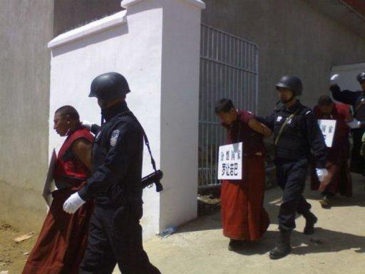 File photo of Chinese paramilitary police guarding monks wearing placards on their necks showing their names and alleged crimes committed in a Tibetan area of southwest China's Sichuan province. The United States warned the world was sliding backwards on religious freedoms Monday, slamming China for cracking down on Tibetan Buddhists and hitting out at Pakistan and Afghanistan