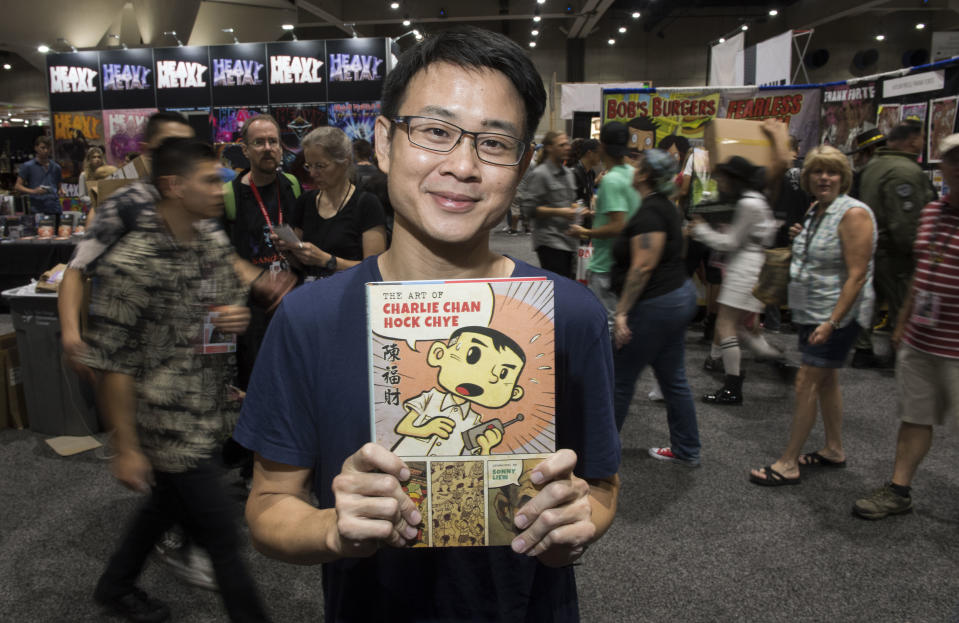 """SAN DIEGO, CA - JULY 21: Graphic novelist Sonny Liew poses with his new book """"The Art of Charlie Chan Hock Chye"""" during day two of Comic-Con International at the San Diego Convention Center in San Diego, CA on Friday, July 21, 2017. (Photo by Kevin Sullivan/Digital First Media/Orange County Register via Getty Images)"""