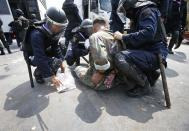 Thai police officers detain an anti-government protester near Government House in Bangkok February 18, 2014. A Thai police officer was killed and dozens of police and anti-government protesters were wounded in gun battles and clashes in Bangkok on Tuesday, officials and witnesses said. REUTERS/Athit Perawongmetha (THAILAND - Tags: POLITICS CIVIL UNREST)
