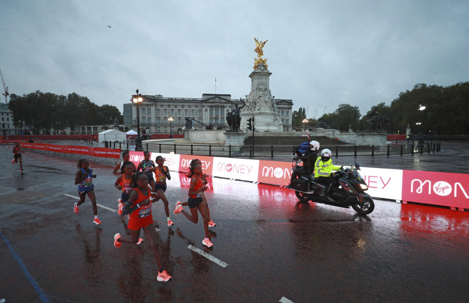 Pacemakers and race leaders run past Buckingham Palace and the Queen Victoria Memorial into the Mall during the London Marathon in London, England, Sunday, Oct. 4, 2020. Athletes are competing on a 26.2-mile (42.2-kilometer) closed-loop course consisting of 19.6 clockwise laps around St. James' Park. The traditional course along the River Thames was scrapped because of the coronavirus pandemic and only elite men and women are competing and no spectators are permitted. (AP Photo/Ian Walton, Pool)