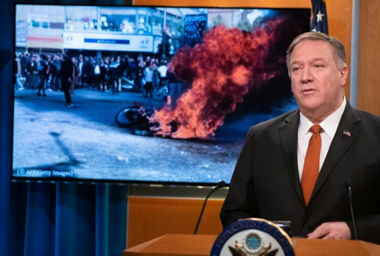 US Secretary of State Mike Pompeo speaks alongside a photograph of demonstrations in Iran (AFP Photo/SAUL LOEB)