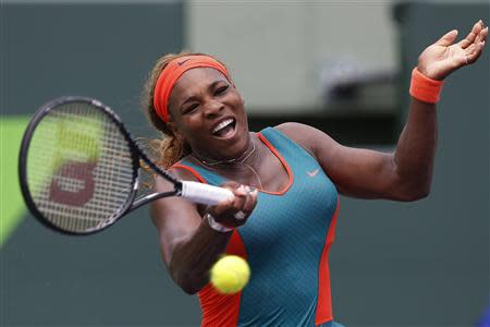 Mar 22, 2014; Miami, FL, USA; Serena Williams hits a forehand against Caroline Garcia (not pictured) on day six of the Sony Open at Crandon Tennis Center. Mandatory Credit: Geoff Burke-USA TODAY Sports