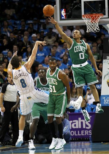 Boston Celtics shooting guard Avery Bradley (0) tries to block a shot by New Orleans Hornets shooting guard Marco Belinelli (8), of Italy, in the first half of an NBA basketball game in New Orleans, Wednesday, Dec. 28, 2011. (AP Photo/Gerald Herbert)