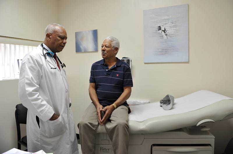 Dr. Sixto Caro, left, speaks with patient Jose Rodriguez at the Medspan Associates clinic on Oct. 3, 2012, in New York City in a Dominican neighborhood in Brooklyn.