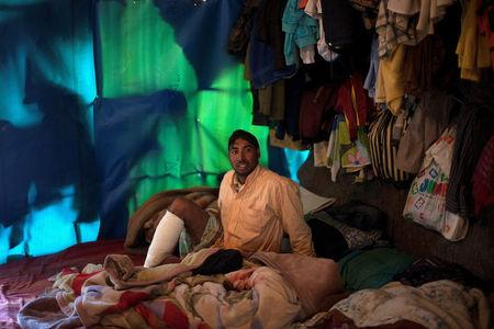 FILE PHOTO: Bangladeshi worker Mohamed, 25, is seen inside a tent following a shooting incident in the of town of Manolada, Greece, April 18, 2013.  REUTERS/Giorgos Moutafis/File Photo