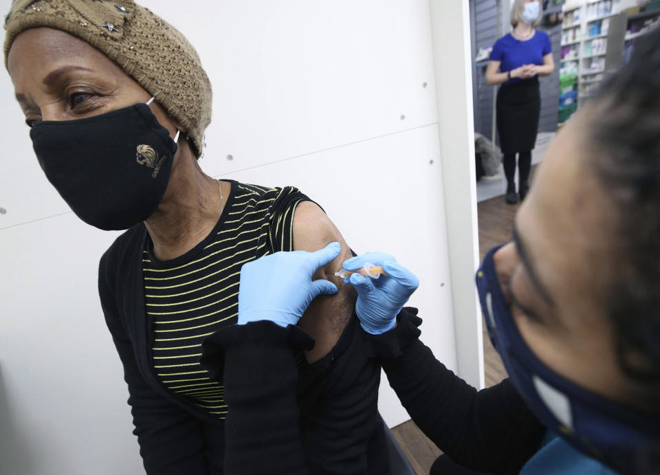 Pharmacist Asha Fowells vaccinates Judy Phillips, aged 75, with her first dose of the Oxford AstraZeneca coronavirus vaccine, at Copes Pharmacy and Travel Clinic in Streatham, south London, Thursday, Feb. 4, 2021. (Yui Mok/PA via AP)