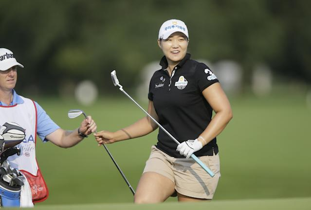 Mirim Lee, right, of South Korea, smiles after her shot from the rough landed near the hole on the 17th green during the third round of the Meijer LPGA Classic golf tournament at Blythefield Country Club, Saturday, Aug. 9, 2014, in Belmont, Mich. (AP Photo/Carlos Osorio)