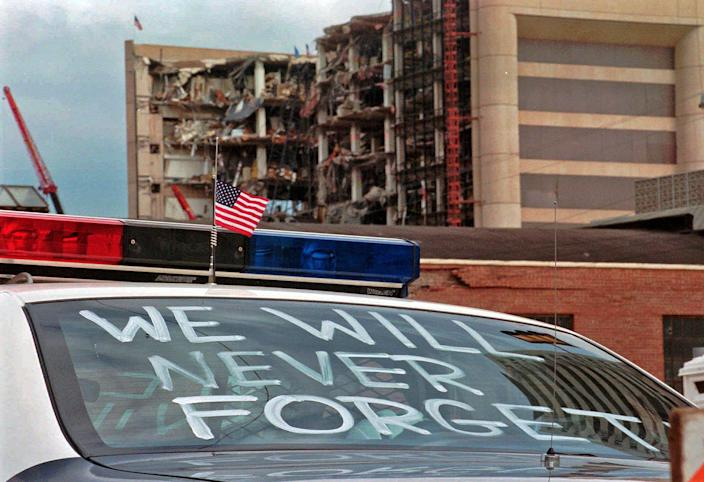"""In this April 24, 1995 photo, an Oklahoma City police car decorated with the words, """"We will never forget"""" and a small American flag sits near the Alfred P. Murrah Federal Building in Oklahoma City. The American terrorist who set the blast killed 168 people, including 19 children. Life changed in the U.S. in its aftermath, with new attention paid to domestic terrorism and beefed up security at federal buildings around the country."""