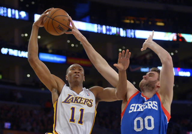 Los Angeles Lakers guard Wesley Johnson, left, has his shot blocked by Philadelphia 76ers center Spencer Hawes during the first half of an NBA basketball game, Sunday, Dec. 29, 2013, in Los Angeles. (AP Photo/Mark J. Terrill)