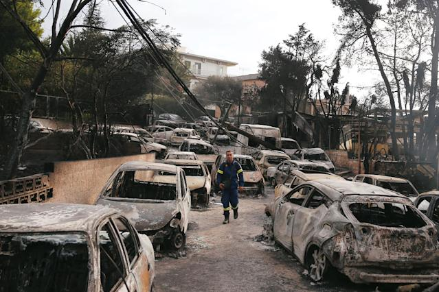 <p>A firefighter walks among burned cars, following a wildfire at the village of Mati, near Athens, Greece, July 24, 2018. (Photo: Costas Baltas/Reuters) </p>
