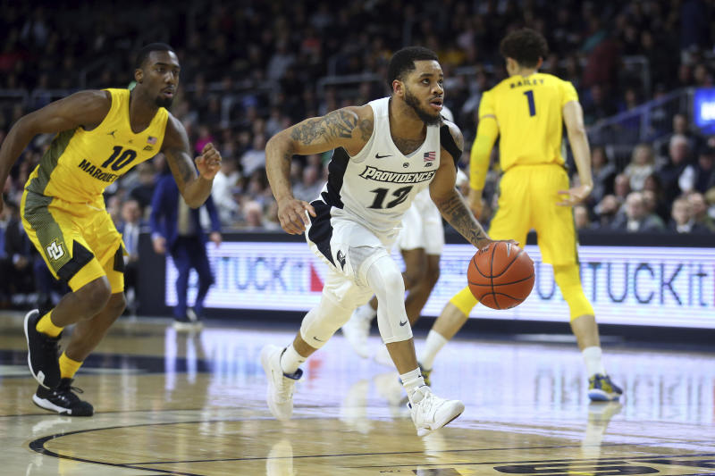 Providence's Luwane Pipkins (12) drives to the basket for a score as Marquette's Symir Torrence (10) follows on the play during the second half of an NCAA college basketball game Saturday, Feb. 22, 2020, in Providence, R.I. (AP Photo/Stew Milne)