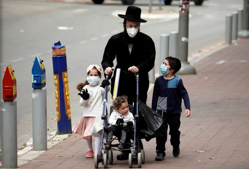 """FILE PHOTO: An ultra-Orthodox Jewish family wearing masks walk on a pavement in Bnei Brak, a town badly affected by the coronavirus disease (COVID-19), and which Israel declared a """"restricted zone"""" due to its high rate of infections, near Tel Aviv"""